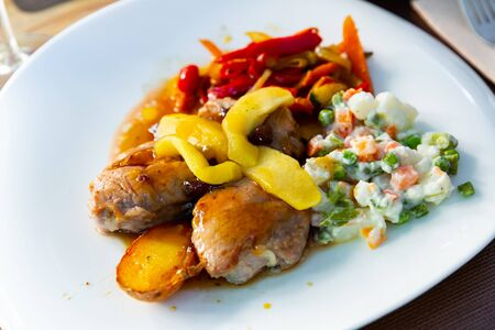 Grilled tasty pork sirloin served with caramelized apple, stewed red peppers and salad from peas and potatoes