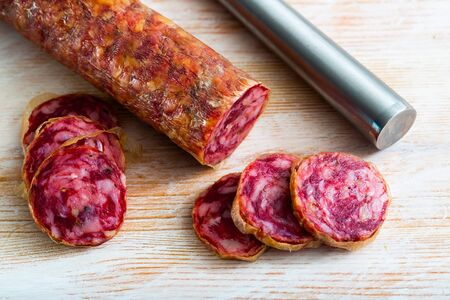 Thin salchichon sausage slices on wooden background, view from above Reklamní fotografie