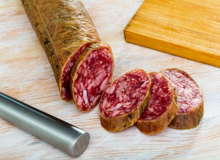 Spanish salchichon sausage cut in slices on a wooden surface, close-up