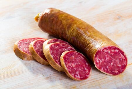 Salchichon spanish sausage slices on wooden desk, view from top