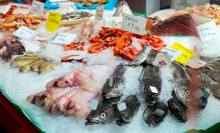 Variety of fresh raw seafoods on crushed ice in open display of fish shop Banque d'images - 130159694