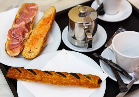 Light European breakfast for two in cafe. Sandwich with cured ham, sweet pastry with chocolate filling, hot espresso and tea
