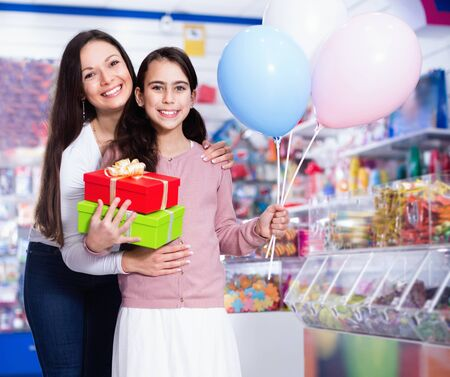Portrait of happy cheerful smiling mother and daughter holding gifts and balloons in store