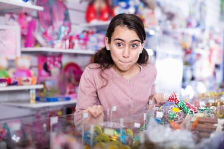 Emotional cheerful positive small girl choosing sweet candies in the candy shop
