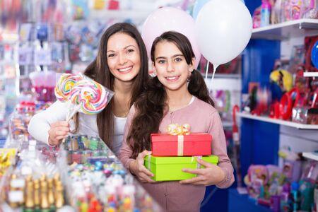 Feliz alegre mujer y niña positiva con regalos y globos en la tienda de golosinas