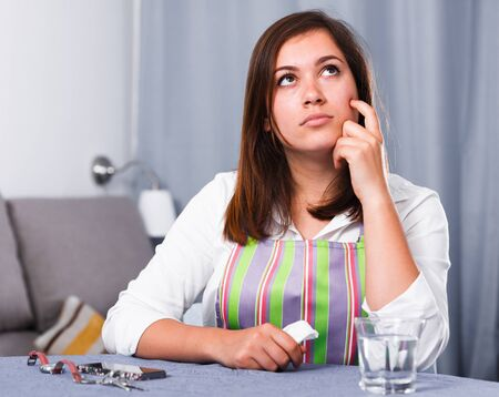 Young woman feeling distressed and lonely alone at home