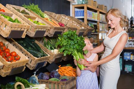 Glad positive young mother with pretty daughter shopping various veggies in food store
