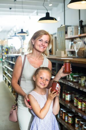 cheerful female customer with little daughter choosing preserve tomato sauce in jar in food shop