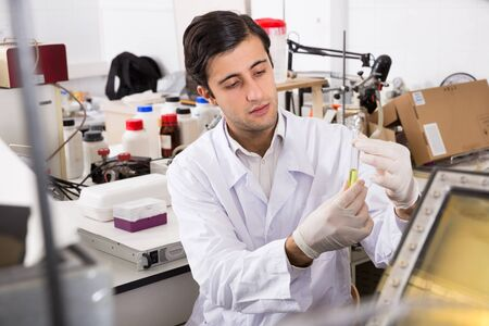 Focused young lab technician working with reagents in test tubes during chemical experiment
