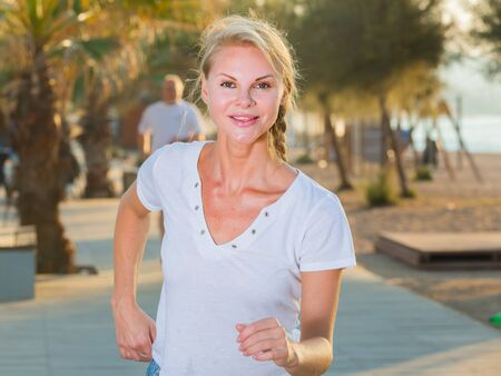 Female in white T-shirt is jogging in the park.