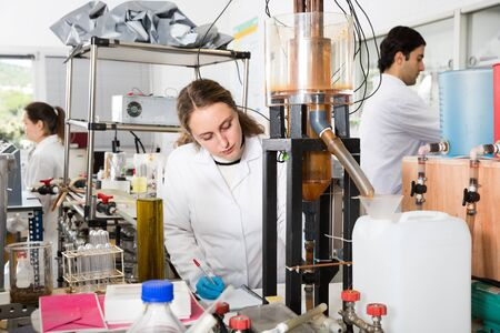 Female student of Faculty of Chemistry working in research laboratory performing experiments on lab equipment Stock Photo