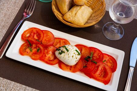 Plate with slices of tomatoes and  mozzarella cheese, dish of Italian cuisine Stock Photo