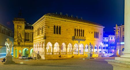 View of lighted Gothic building of Loggia del Lionello - town hall of Udine on central city square of Piazza liberta, Italy