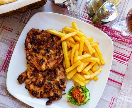 Traditionelles Balkangericht Pileci Batak, gegrillte Hähnchenschenkel ohne Knochen, serviert mit Pommes Frites und Sauce Standard-Bild