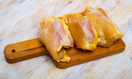 Raw skinless chicken thighs on cutting board