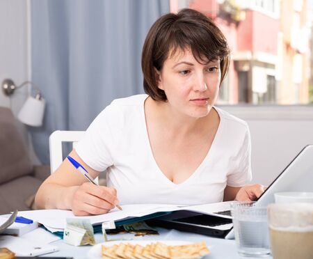 Woman sitting at table at home calculating domestic finances and bills