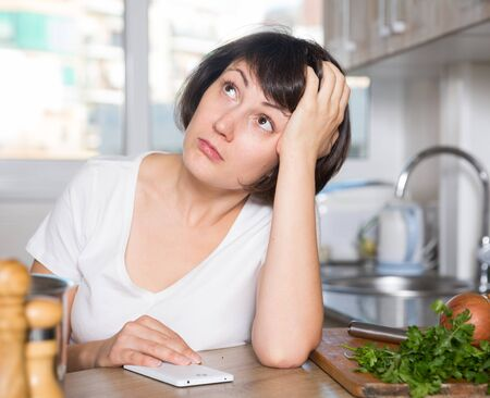 Portrait of adult sad woman tired of worries at kitchen