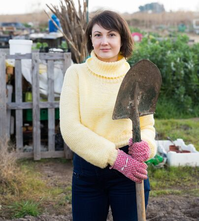 Portrait of smiling young woman working with shovel in vegetables garden
