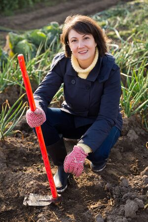 Young woman farmer working with hoe in vegetable garden, hoeing the soil
