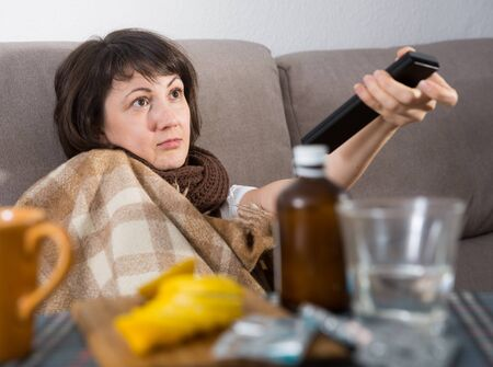 Sick woman watching tv switching channels by remote control at home