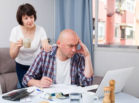 Wife calms husband who is upset about financial results.