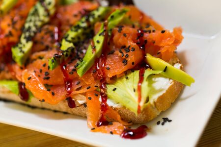 Salmon toast with lettuce, avocado and cheese is tasty dish in the kitchen.