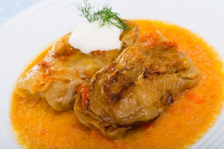 Traditional dish of Balkan cuisine - stuffed cabbage leaves with fresh sour cream and herbs