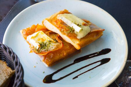 Traditional Catalan focaccia baked with caramelized onion, bacon slice, Brie cheese and seasonings