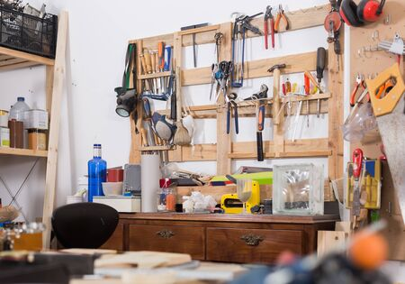 Old tools hanging on wall in workshop, tool shelf against a wall in family garage