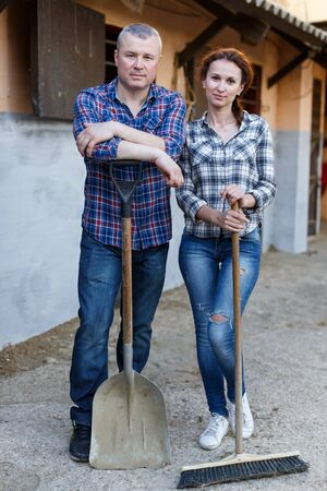 Portrait of smiling couple with tools standing at farm outdoor Фото со стока