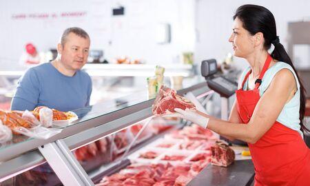 Venditore di donna che aiuta il cliente maschio a scegliere la carne in macelleria Archivio Fotografico