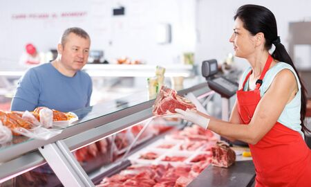 Woman seller helping male customer choosing meat in butcher's shop Imagens