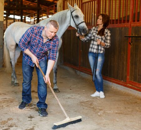 Male worker cleaning floor at stabling, woman farmer standing with horse Фото со стока