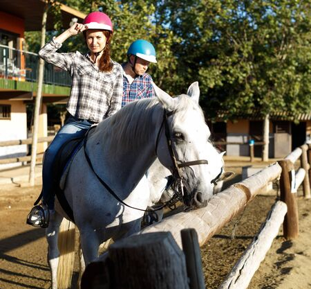 Portrait of woman and man in helmets training riding horse at farm at summer day Reklamní fotografie