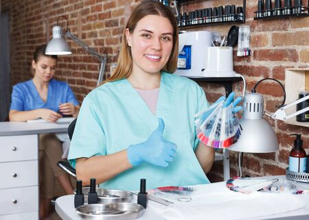 Young happy girl manicurist in gloves sitting at her workplace in modern nail salon