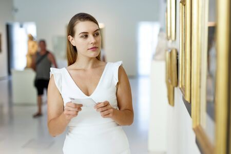 Portrait of attractive girl with guide brochure looking at paintings in art museum
