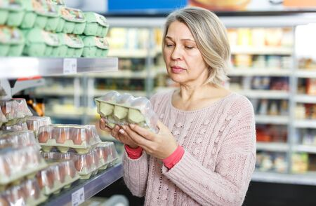 Middle aged woman choosing and buying fresh eggs at grocery store