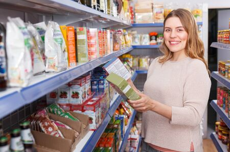 Adult female customer choosing groats in  grocery food store Stock Photo