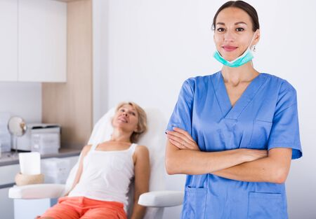 Portrait of qualified female cosmetologist smiling confidently in medical center