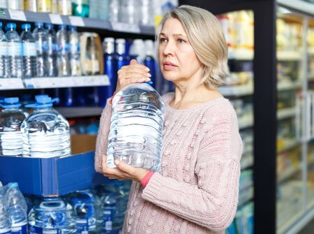 Adult woman looking for water in bottles in food store