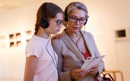 Teenage girl and mature woman using audio guide during excursion in historical museum