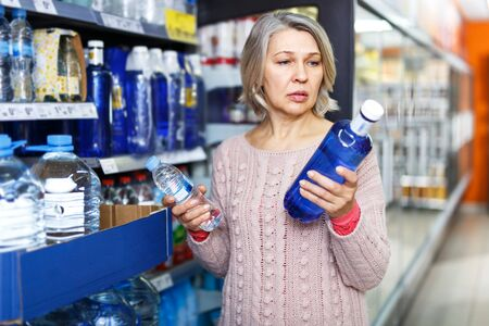 Casual aged woman purchasing still water in food department of supermarket