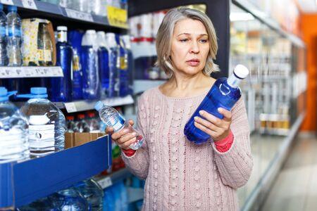 Casual gealterte Frau kauft stilles Wasser in der Lebensmittelabteilung des Supermarkts?
