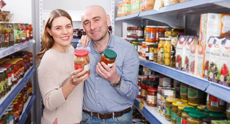 Smiling woman and husband  choosing pickle goods in the supermarket