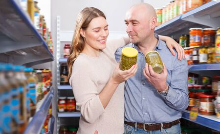 Glad couple in the store choosing preserved goods in grocery section