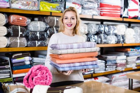 Young happy cheerful female customer boasting purchased home textiles in textile shop