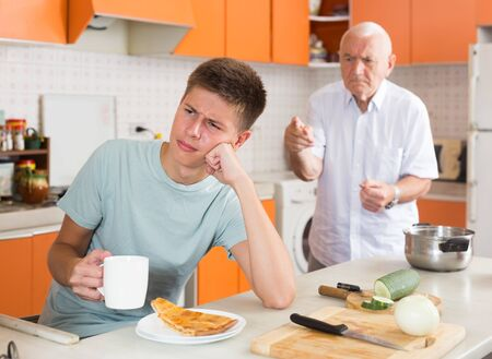 Frowning teen boy sitting at kitchen table, listening to reprimanding from his disgruntled grandfather