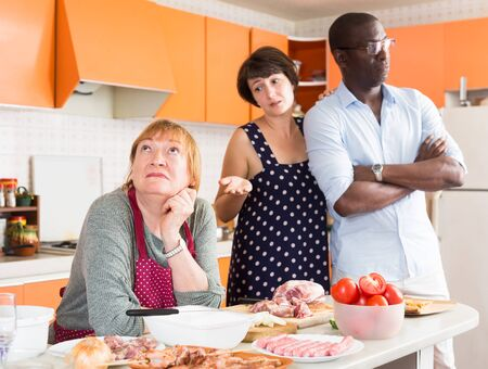 Portrait of offended dissatisfied elderly woman during home quarrel with daughter and her African husband Stock Photo