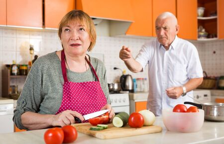 Portrait of upset aged woman cooking in home kitchen on background with scolding husband