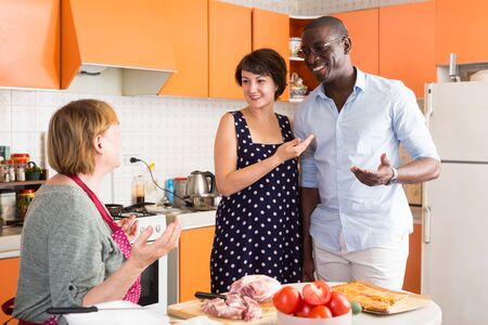 Aged woman glad to get acquainted with future husband of her adult daughter, talking to them at home kitchen